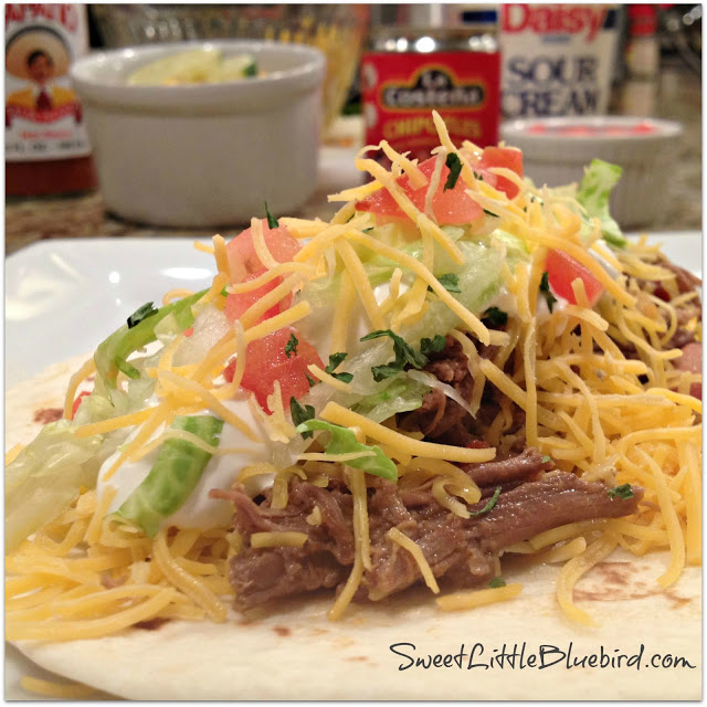 EASY SLOW COOKER SHREDDED BEEF TACOS - Shredded beef on small flour tortilla taco topped with lettuce, tomato, sour cream and cheddar cheese