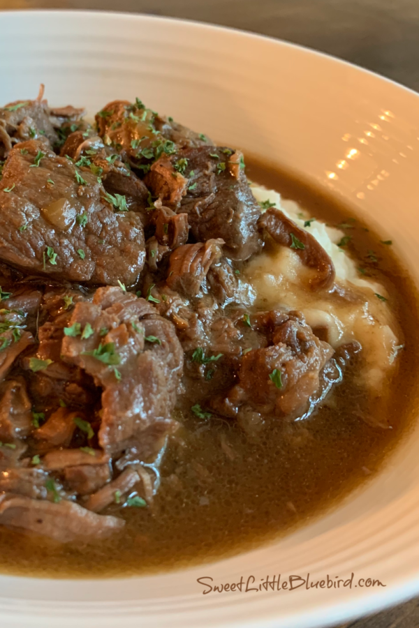 Best Ever Beef Tips made in the Slow Cooker - plated in a bowl, mashed potatoes with beef tips and gravy on top.