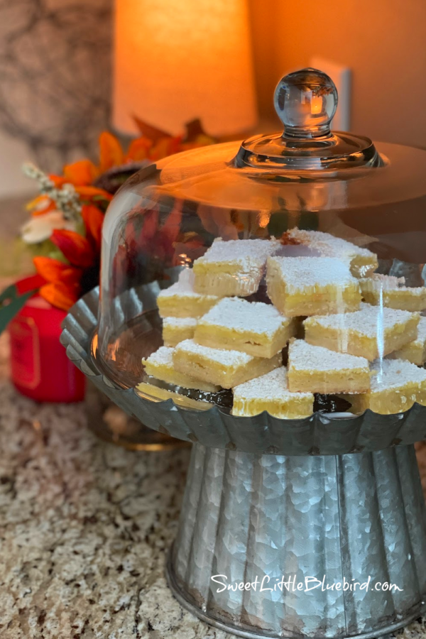 Nancy's Deluxe Lemon Bar Squares stacked in layers on clear glass cake plate with with cover.