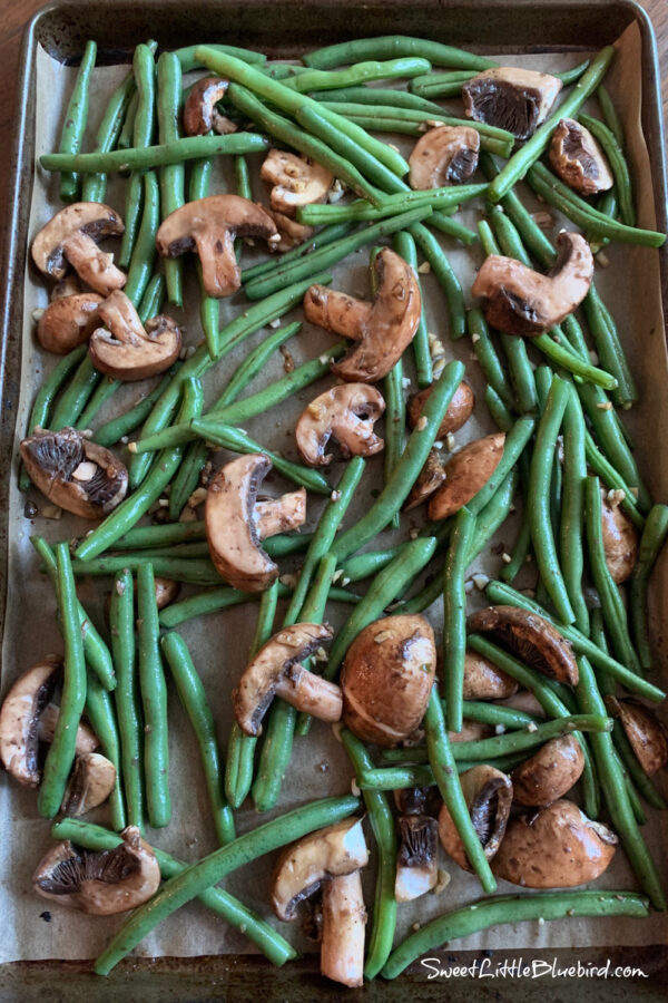 Easy Oven Roasted Green Beans and Mushrooms placed evenly on baking sheet with parchment paper for raosting in oven.